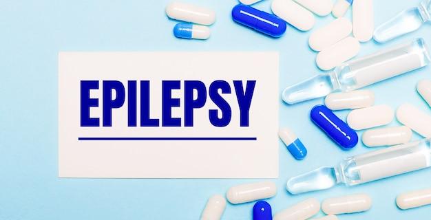 Таблетки, ампулы и белая карточка с текстом эпилепсия на голубом фоне. медицинская концепция