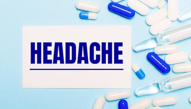 Таблетки, ампулы и белая карточка с текстом «головная боль» на голубом фоне. медицинская концепция