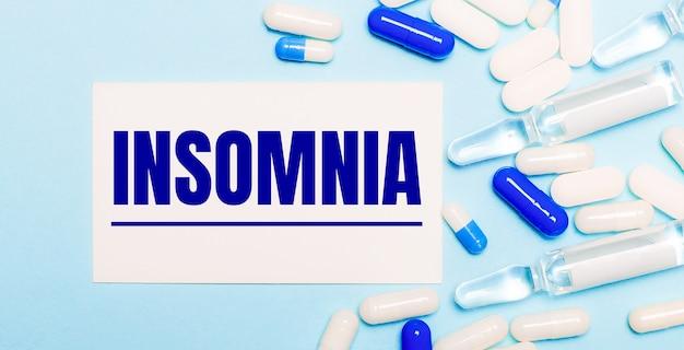 알약, 앰플 및 밝은 파란색 배경에 텍스트 insomnia가있는 흰색 카드