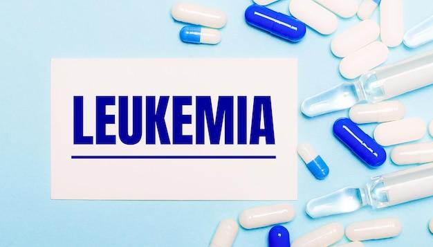 Таблетки, ампулы и белая карточка с текстом лейкемия на голубом фоне. медицинская концепцияv