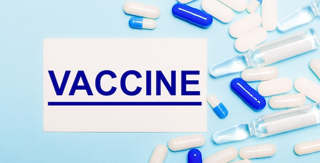 Таблетки, ампулы и белая карточка с текстом вакцина на голубом фоне. медицинская концепция