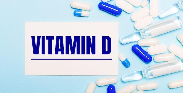 알약, 앰플 및 밝은 파란색 배경에 텍스트 비타민 d가있는 흰색 카드. 의료 개념