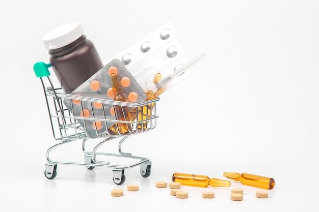 Pills, ampoules and syringe for injection in a market basket on a white background. business and medicine