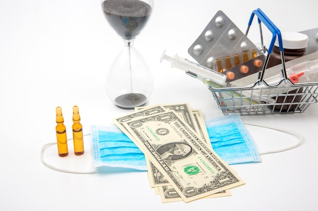 Pills, ampoules and syringe for injection, medical mask, money and hourglass on a white background. business and medicine.