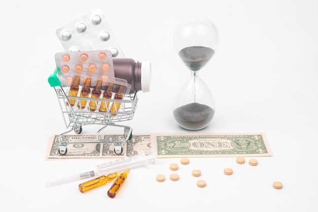 Pills, ampoules and syringe for injection, money dollars and hourglass on a white surface. business and medicine.