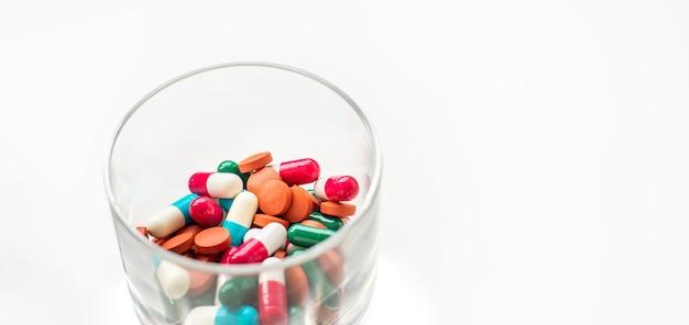 Таблетки и капсулы в стакане коктейль из лекарств мониторинг лечения противовирусными препаратами