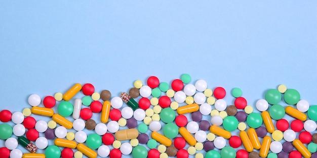 Таблетки и капсулы разного цвета беспорядочно разбросаны на бледно-голубом фоне.