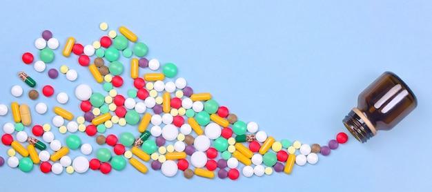 さまざまな色の錠剤やカプセルが淡い青色の背景のガラス瓶から飛び出しますワイドフォーマットのバナー