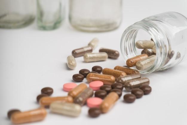 白い背景に散らばっている錠剤やカプセル