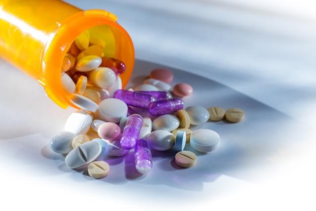 Таблетки и лекарства, выливающиеся из оранжевой бутылки на белом фоне