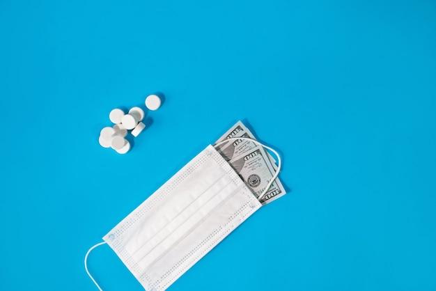 Таблетки и медицинская маска для лица покрывали стодолларовую купюру на синем фоне.