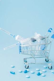 Таблетки и медицинские инъекции в тележке для покупок на синем фоне. творческая идея стоимости здравоохранения, аптеки, медицинского страхования и бизнес-концепции фармацевтической компании. копировать пространство