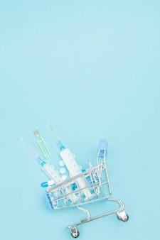 Таблетки и медицинские инъекции в тележке для покупок на синем фоне. творческая идея стоимости здравоохранения, аптеки, медицинского страхования и бизнес-концепции фармацевтической компании. скопируйте пространство.