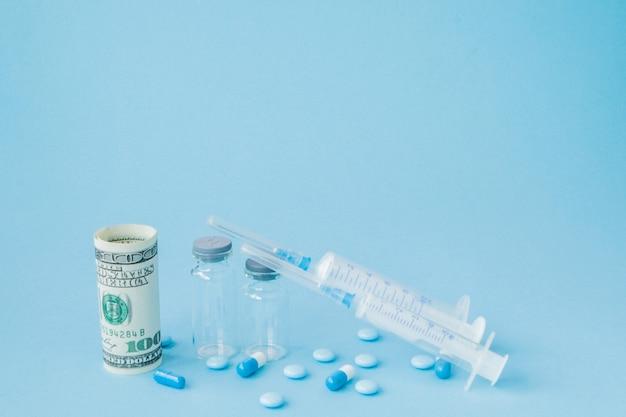 薬と青色の背景に医療用注射。医療費、ドラッグストア、健康保険、製薬会社のビジネスコンセプトの創造的なアイデア。