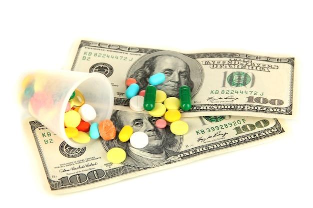 Таблетки и деньги, изолированные на белом фоне