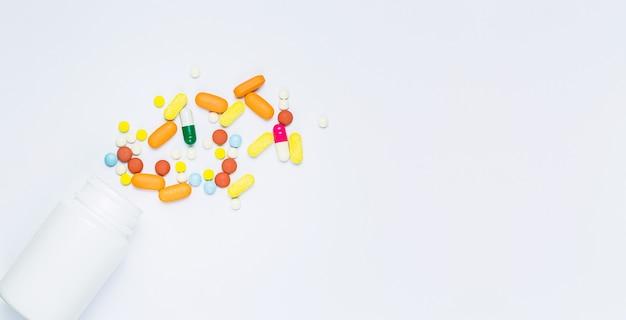 白い背景の上の丸薬と丸薬瓶こぼれた丸薬瓶が分離されました