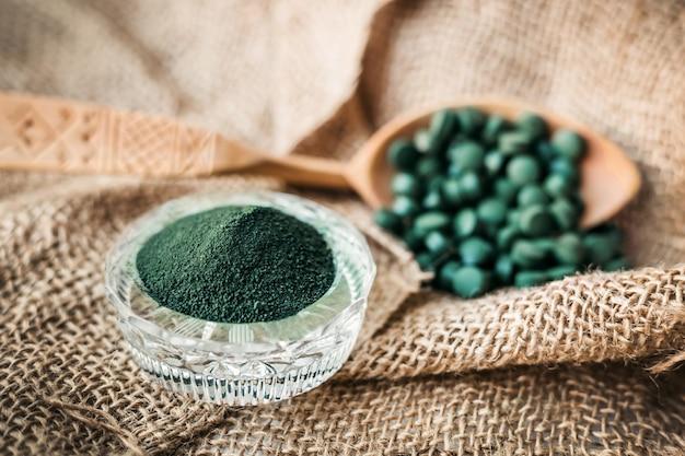 海藻スピルリナ、木のスプーンのクロレラの丸薬と粉末がクローズアップ。植物性タンパク質を含むベジタリアンスーパーフード。海洋性ビタミン、ミネラル