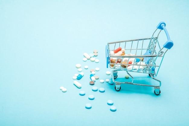 青い背景の上の丸薬とショッピングトロリー。医療費、ドラッグストア、健康保険、製薬会社のビジネスコンセプトに関する独創的なアイデア。スペースをコピーします。