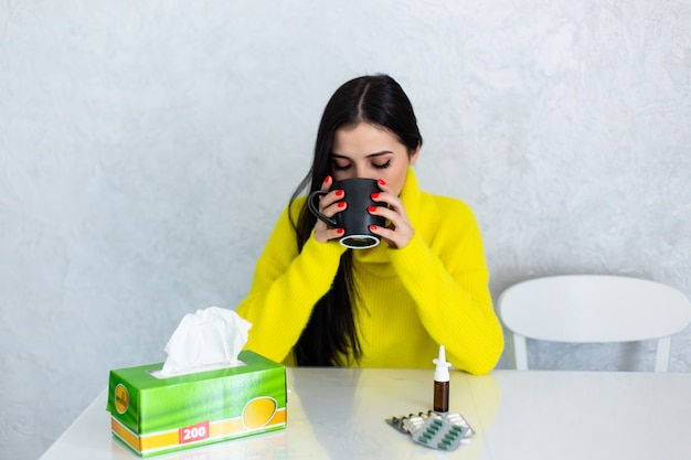 薬とお茶。若い女性は薬を服用し、熱いお茶を飲む