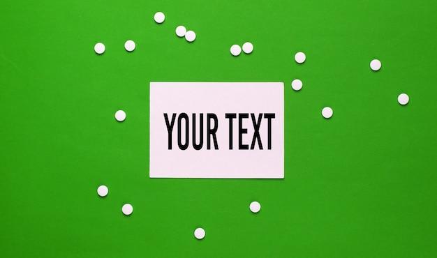 Таблетки и белый лист бумаги для копирования пространства на зеленом фоне. вид сверху. концепция медицины минимализма