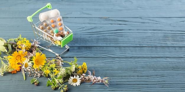 薬と木製のテーブルの野生植物