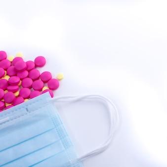 Таблетки антибиотиков и витаминов и защитные медицинские маски для лица.
