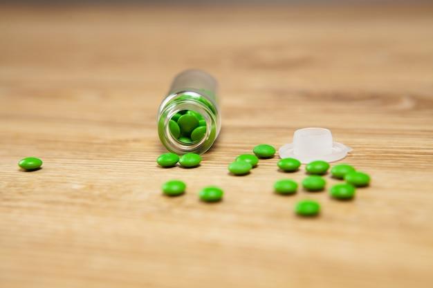 錠剤はテーブルの上の容器から散らばっています
