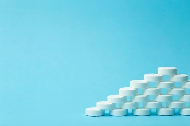 薬の背景。薬、ドラッグ、薬のコンセプト。青色の背景に白い錠剤
