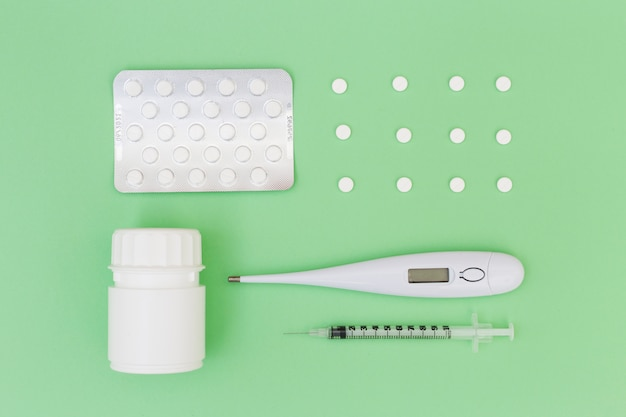 Pills; blister pack; thermometer; plastic bottle and syringe on green background