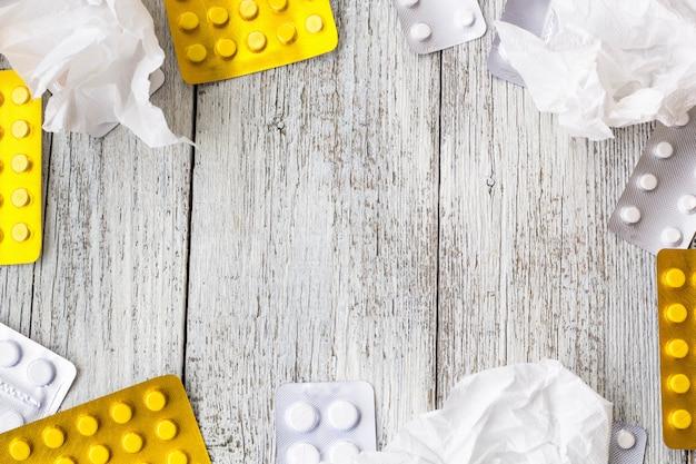 丸薬の境界線。ビタミン、錠剤、ブリスターパックの丸薬、白い木製の背景にしわくちゃのハンカチ。