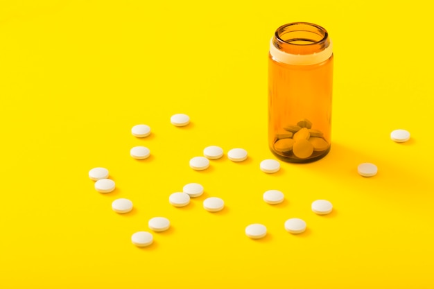 Pills bottle and circular white medicine on yellow background