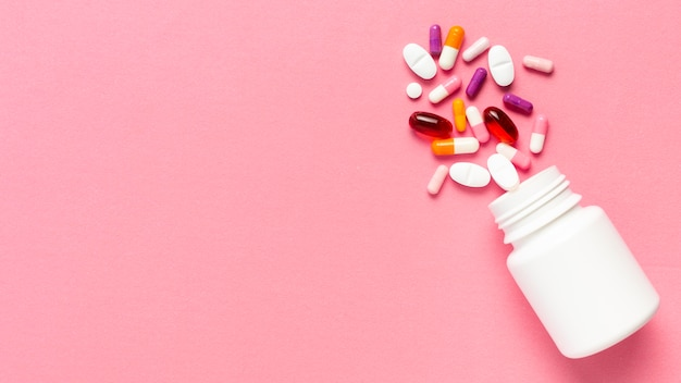 Pills bottle on pink background