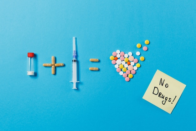 Бутылка таблеток плюс игла шприца равны красочным круглым таблеткам лекарства в форме сердца, изолированному на синем фоне