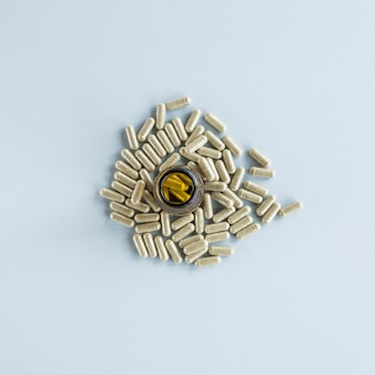 Pills bottle surrounded with capsules over colored background