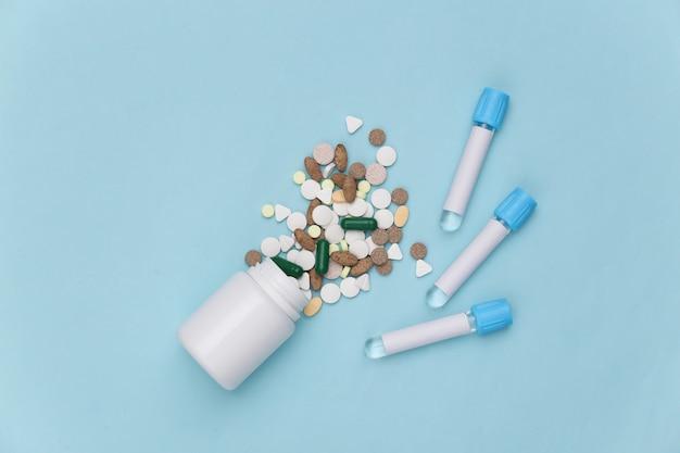 파란색 배경에 의료 테스트 튜브가 있는 알약 병. 평면도