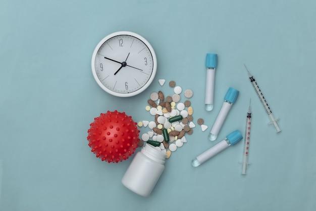 의료 테스트 튜브, 바이러스 변형 모델, 주사기, 파란색 배경에 시계와 약 병. 치료. 코로나 19 감염병 세계적 유행. 평면도