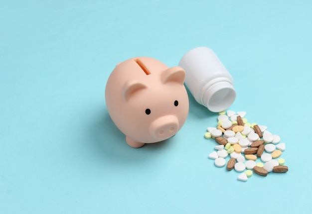Pills bottle with piggy bank on blue pastel