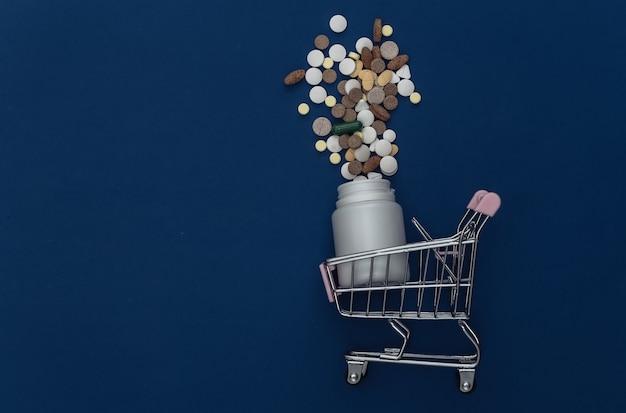 고전적인 파란색 배경에 쇼핑 트롤리가 있는 알약 병. 색상 2020. 상위 뷰.