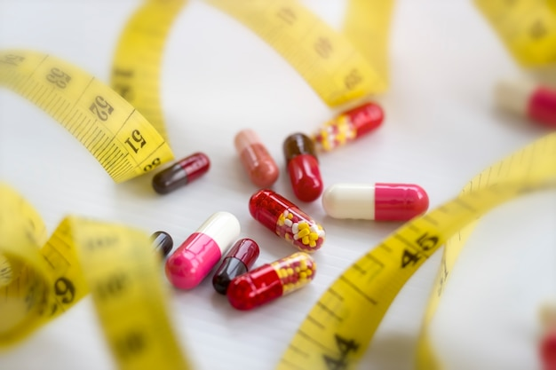 Pills, capsule with measuring tape on white