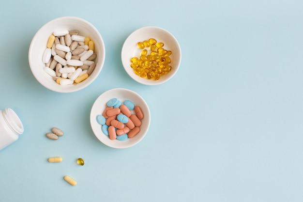 水色の背景の白いプレート上の錠剤、カプセル、ビタミン、天然有機食品サプリメント。最小限の現代的な薬局またはヘルスケアの概念。フラットレイ、上面図、コピースペース。