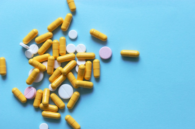 Pills on a colored background top view closeup medicines vitamins