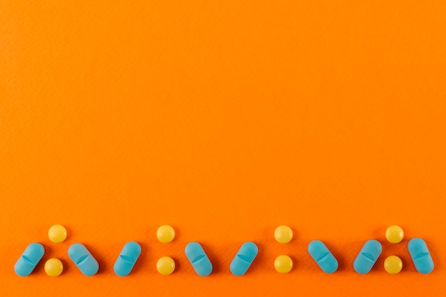 Pills design made on an orange colored backdrop