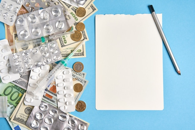 Таблетки пустые блистеры для наркотиков индивидуальный шприц и деньги лежат на синем фоне