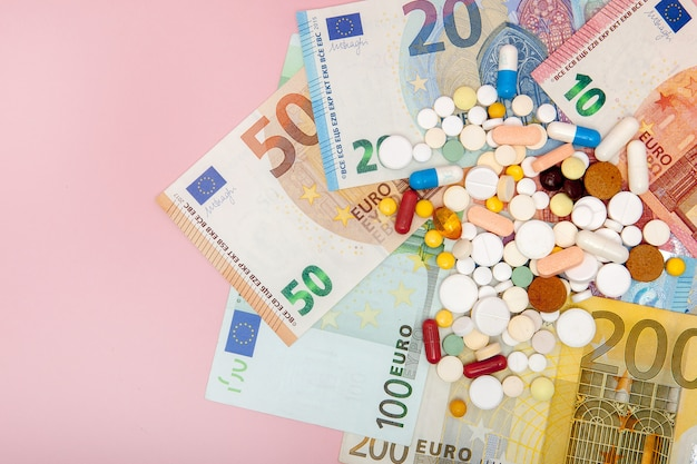 A pills and euro on a pink with copy space.