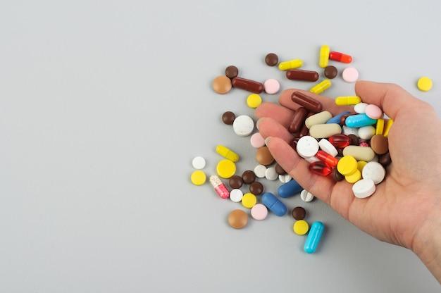 錠剤は灰色の背景に女性の手のひらから落ちます。ヘルスケアの概念。 covid-19(新型コロナウイルス感染症)(#文字数制限がない場合、初出時にかっこ書きを追加;コロナウイルス;処理;ウイルス;コピースペース