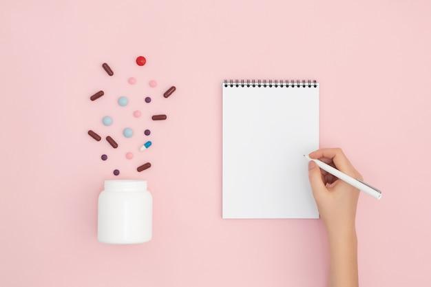 白い瓶からの丸薬が淡いピンクの上に散らばっていて、手がノートに書いています。