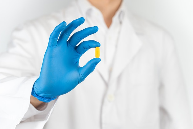 Pills in the hands of a doctor wearing gloves