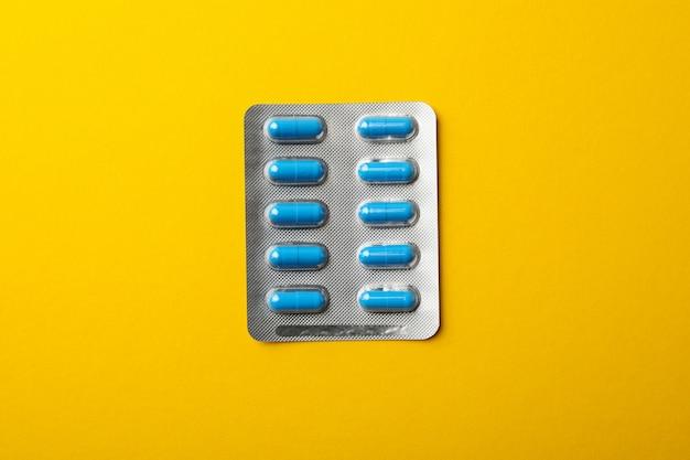 Таблетки в блистерной упаковке на желтом фоне, место для текста