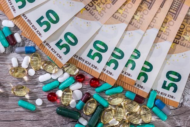 木製の机の上にユーロ紙幣とカプセルの丸薬