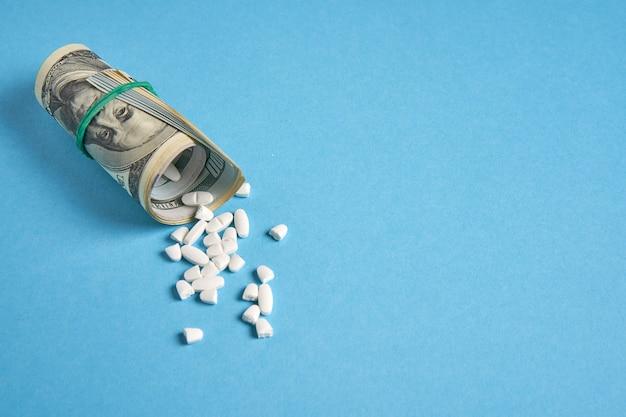 Таблетки в свернутых долларовых купюрах